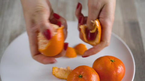 Women's hands peel the peel of tangerine, mandarin slices are piled on a plate Footage