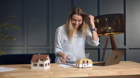 Young female architect working on the new desing of house using 3d house model Live Action