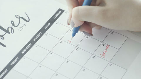 Macro of the hand writing a word deadline in the schedule under the date of 11 Live Action