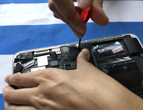 user of Apple Mac book laptop is showing how to change battery Photo