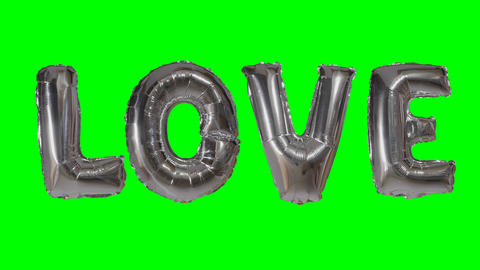 Word love from helium silver balloon letters floating on green screen Archivo