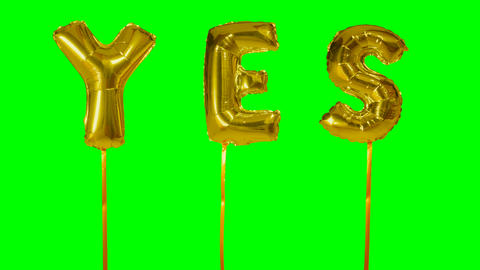 Word yes from helium golden balloon letters floating on green screen Live Action