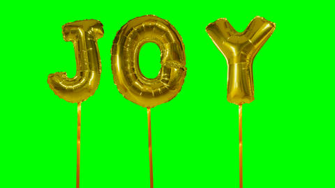 Word joy from helium golden balloon letters floating on green screen Footage