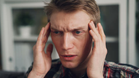 Close-up shot of unhealthy guy touching his head because of migraine massaging Footage
