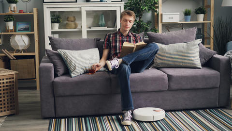 Carefree person is reading book, drinking tea sitting on sofa in apartment while Live Action