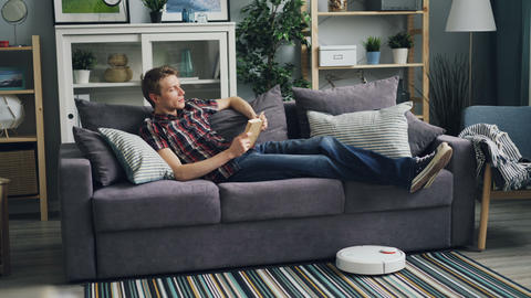 Relaxed young man is reading book at home enjoying modern literature while Footage