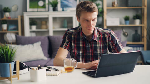Successful male freelancer is working at home using laptop sitting at desk in Footage