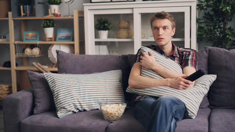 Emotional young man is watching horror film on TV at home, eating popcorn and Live Action