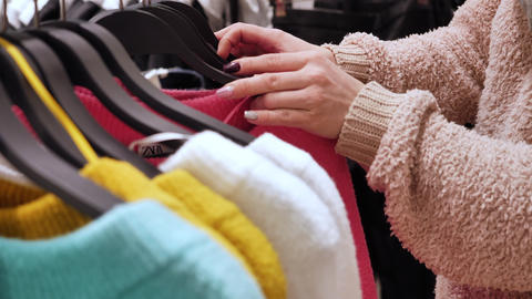 Woman chooses a sweater in a clothing store Live Action