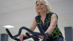 Middle aged blonde woman is doing exercises on stationary bike. Sport concept Archivo