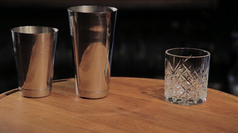 Cocktail shaker and beaker for preparation beverages on bar counter in pub close Live Action