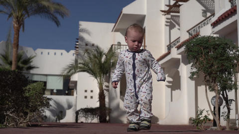 A little baby clumsily walks along a road in a tropical area in slow motion Footage