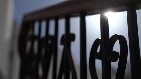 A ray of sunshine penetrates a beautiful forged fence in slow motion Live Action