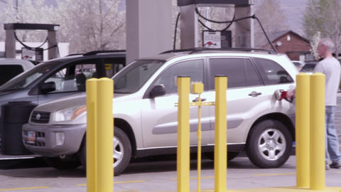 Panning shot of vehicles at a gas station Footage