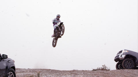 Motorcycle jumping over hill between two SUVs Live Action