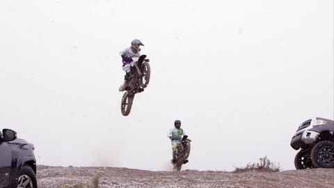 Two motorcycles jumping over hill between two SUVs Live Action