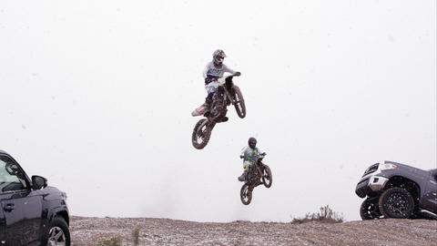 Two motorcycles jumping over hill between two SUVs in the falling snow Footage