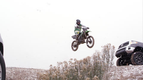 Motorcycle jumping over hill between two SUVs in the falling snow Footage
