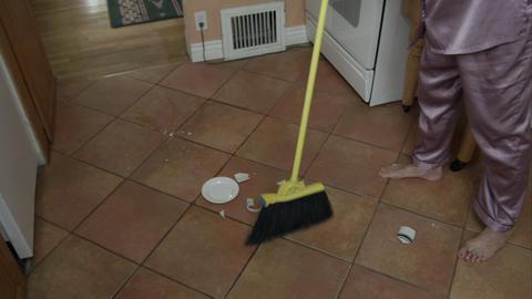 Woman in pajamas cleaning up broken tea cup on floor Live Action