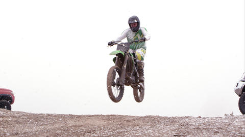 Motocross rider jumping over hill between two SUVs Footage