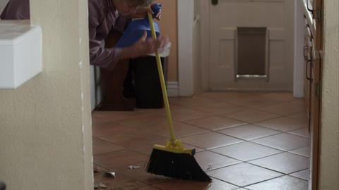 Woman in pajamas sweeping up broken tea cup Live Action