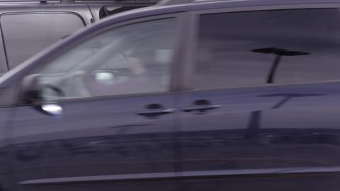 Black SUV fueling as minivan pulls in Footage