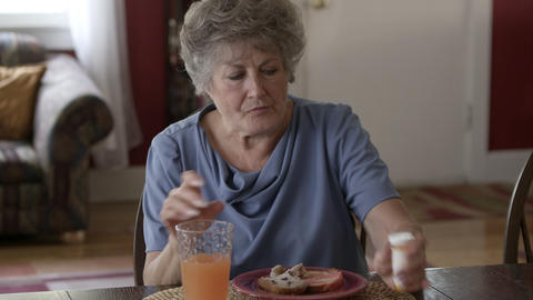 Elderly woman eating breakfast and taking pills Live Action