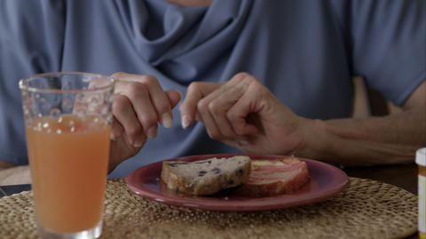 Tight shot of elderly woman eating breakfast and taking pills Live Action