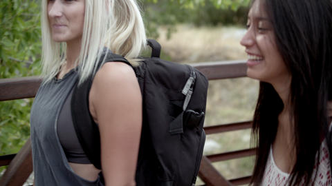Shot from the side of two girls hiking across a bridge Stock Video Footage