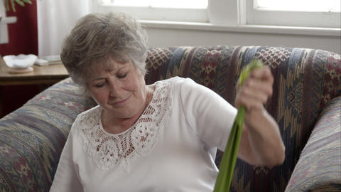 Tight shot of elderly woman doing exercise with elastic bands at home Live Action