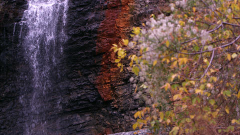 Panning shot of a waterfall with autumn foliage in the foreground Footage
