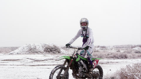 Man riding motorcycle in desert snow Footage