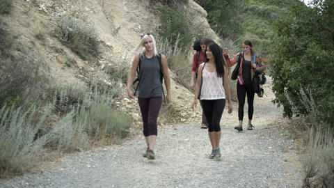 Four friends hiking and talking, walking toward the camera Footage