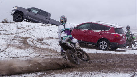 Motorcycle spinning out in dirt with toyotas in the background Footage