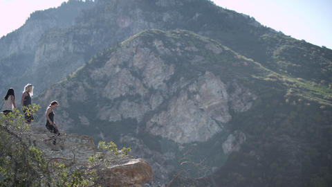 Four people hiking out on a mountain rock outcropping Footage