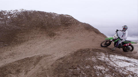Motorcycle riding up and across hill in falling snow Footage