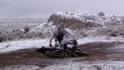Man getting up from laid down motorcycle in snowy desert Footage