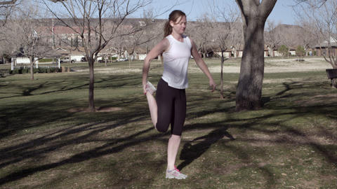 Woman in athletic clothing stretching in the park Live Action