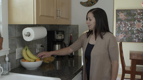 Woman picking fruit over junk food in kitchen Live Action