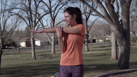 Woman wearing athletic clothing stretching arms in the park Footage