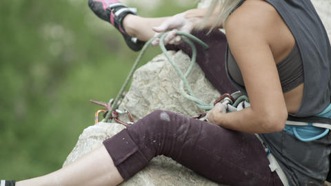 Rock climbing woman untying rope from harness Footage