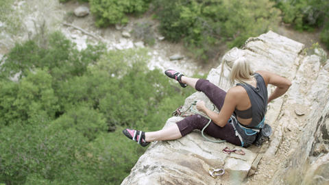 Rock climbing woman at top of route untying rope and retrieving gear Footage