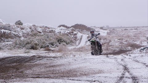 Man riding motorcycle in snowy desert Footage