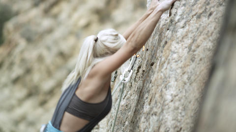 Woman rock climbing and topping out Footage