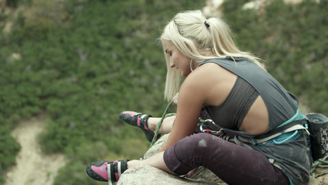 Rock climber woman belaying from the top of the route Footage