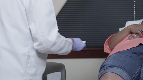 Doctor putting on gloves and sanitizing injection site on woman's knee Footage