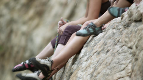 Three women at the top of a rock climbing route hanging feet over the edge Footage