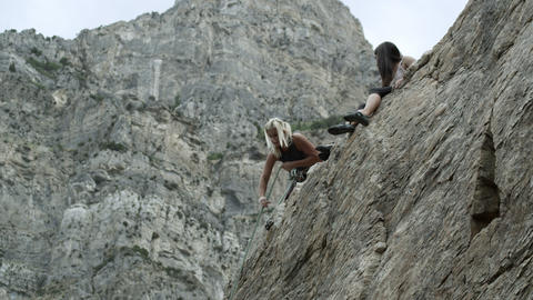 Woman adjusting rope hanging over rock cliff Footage