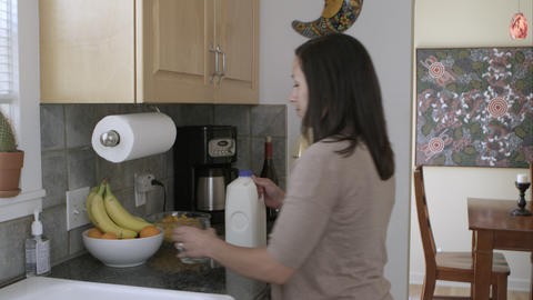 Woman pouring a glass of milk in the kitchen Live Action