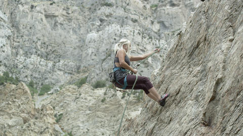 Blonde woman rappelling down rock face Footage